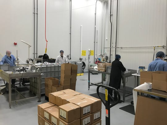 Production workers at Drinkworks in Williston making hand sanitizer for local use.