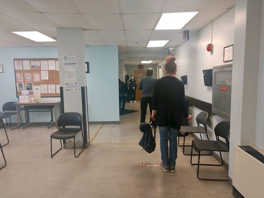 Two clients at Crossroads Clinic in Corryville wait on marked 6-foot intervals for methadone medication during the COVID-19 pandemic in April. A security card with a medical masks stands at the exit.