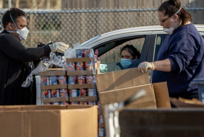 A woman watches from her car while in line as workers fill bags with food to be handed out during a food distribution by Gleaners Community Food Bank at the Jefferson Barns Community Vitality Center in Westland on Monday, April 20, 2020.