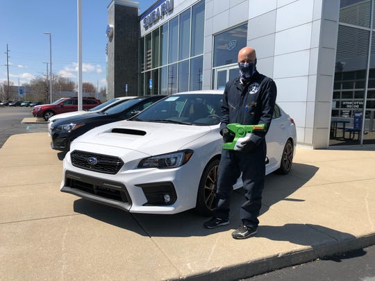 Legacy Service Solutions CEO Jim Ales holds the spray gun used to disinfect in front of Sellers Subaru.