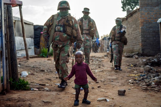 South African National Defense Forces patrol the Sjwetla informal settlement after pushing back residents into their homes, on the outskirts of the Alexandra township in Johannesburg, Monday, April 20, 2020.