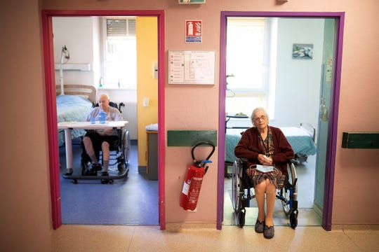 Marie Lithard, right, and her neighboor Yves Chretien sit looking out of their rooms in a nursing home in Ammerschwir, France Thursday April 16, 2020.