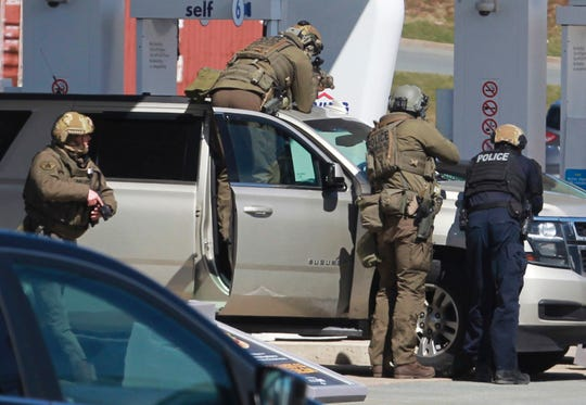 Royal Canadian Mounted police officers surround a suspect at a gas station in Enfield, Nova Scotia, Sunday April 19, 2020. It was the deadliest shooting in Canada in 30 years.