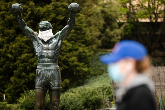 A person wearing a protective face mask as a precaution against the coronavirus walks past the Rocky statue outfitted with mock surgical face mask at the Philadelphia Art Museum in Philadelphia.