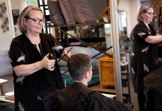 Christel Lerche cuts a customer's hair at Hot N Tot Hairdressers, in Bagsvaerd, Denmark, Monday, April 20, 2020. Denmark began reopening hair salons, dentists, physiotherapists, tattoo parlors and driving schools, among others on Monday which had previously been closed amid the coronavirus pandemic.