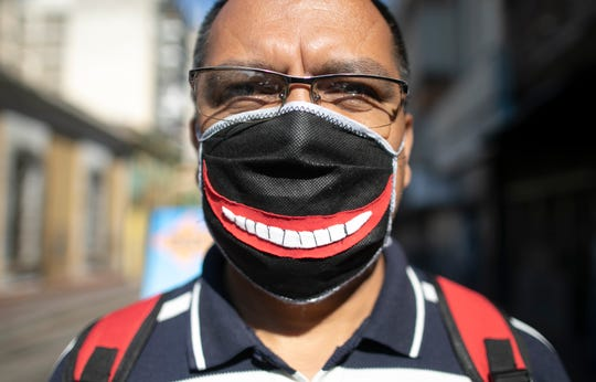 A man wears a face mask with a smile, to protect himself from the spread of the new coronavirus in Caracas, Venezuela.