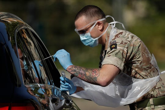 A National Health Service worker is tested by a soldier for COVID-19 at a drive-through testing center in a car park in Chessington, Greater London, Monday, April 20, 2020.