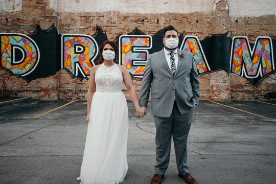 """Hayley and Austin Felch wear masks in a wedding portrait taken in front of the """"Dream"""" mural on March 21, 2020, in Green Bay, Wis."""