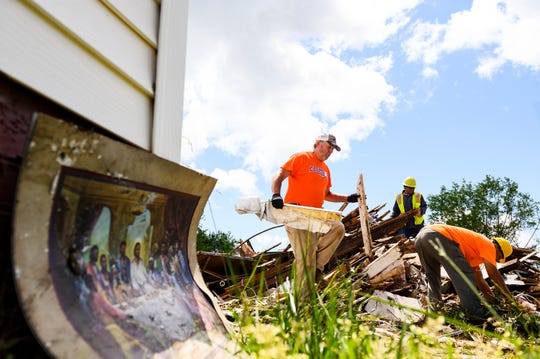 Workers clear out debris from a home that was destroyed in Seneca Monday, April 20, 2020 after an EF3 tornado with 160 mph winds swept through the area last week.