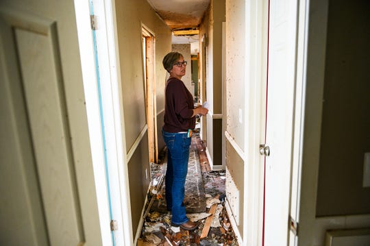 Kelli Patterson walks through the hallway of her home in Seneca Monday, April 20, 2020. Patterson's home was extensively damaged after an EF3 tornado with 160 mph winds swept through the area last week.
