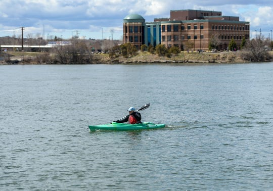Allan Standiford does laps in his kayak across the Missouri River in between West Bank Park and Sight and Sound Park on Sunday, April 19. State and local tourism officials are promoting the state's outdoor recreation, but how quickly the state's tourism industry will rebound is  unclear.