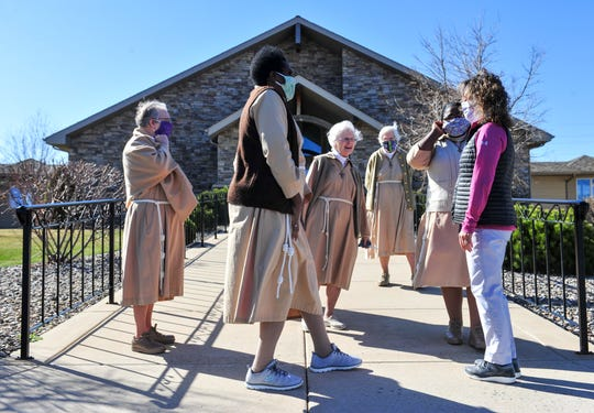 The sisters of Poor Clare Monastery visit with Cari Yturri after their prayer to the city of Great Falls and its medical professionals in front of their monastery on Monday morning.
