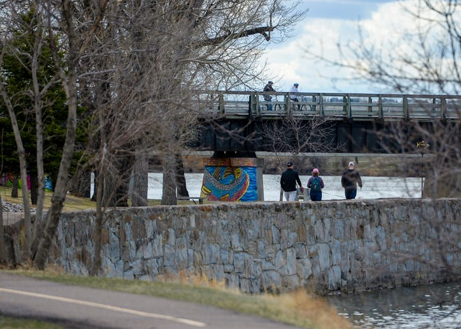 People bike and walk the River's Edge Trail along the Missouri River near the Central Avenue West Bridge on Sunday, April 19, 2020.