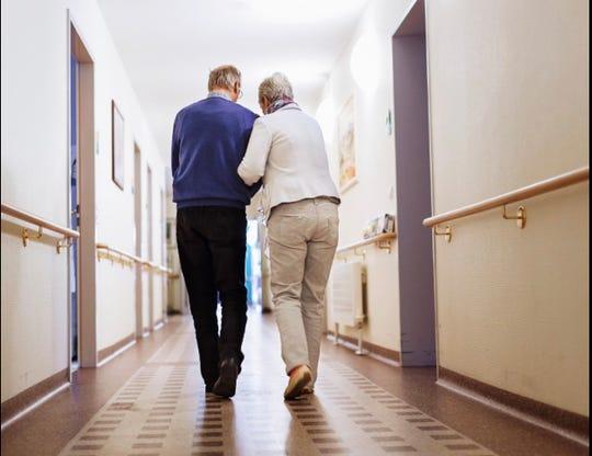 Senior couple walks along a corridor in a nursing home.