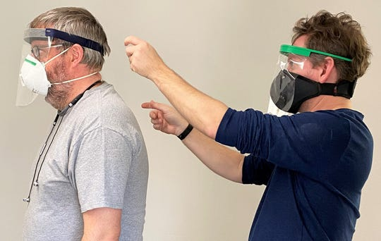 Kirk Cheyney, right, prepares to adjust the mask of volunteer Eric Engelmann during a Sunday session of making face shields at Iowa City FabLab. The local non-profit has a goal to make and give away 4,000 shields, most to nursing homes throughout the area.