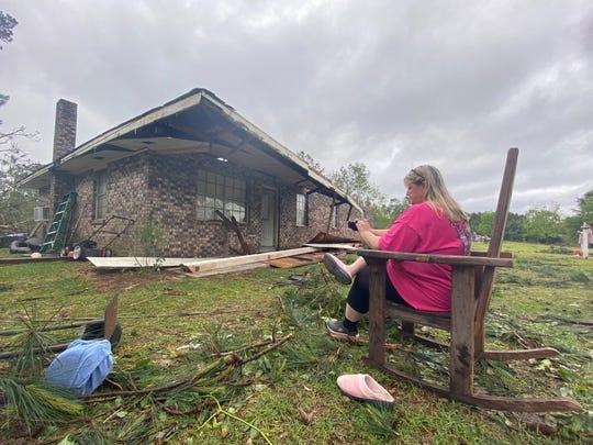Penny Temples, a teacher at Lumberton High School, assesses damage April 20, the morning after a tornado struck Baxterville, Miss.