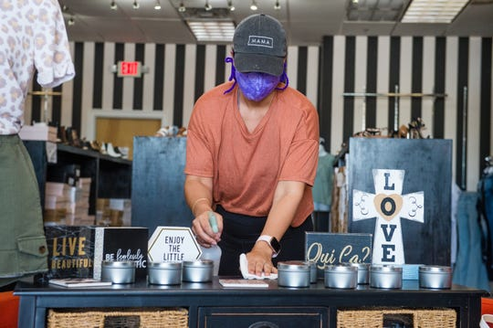 Jordan Patin disinfecting counter tops at Shoetique on Hector Connoly Rd in Carencro. Monday, April 20, 2020.
