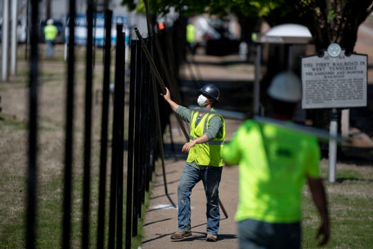 Workers from West Memphis Fencing work to install a fence Monday, April 20, 2020, at the former Commercial Appeal building on Union Avenue in Memphis. The building is being converted to a COVID-19 overflow hospital.