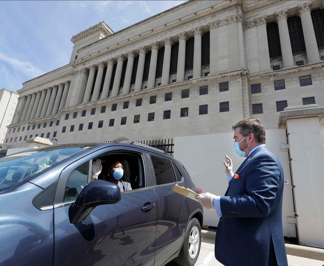 Marcelia Nicholson, County Board supervisor from District 5, is sworn in Monday by Milwaukee County Clerk George Christenson in the Courthouse Annex parking lot outside the Milwaukee County Courthouse. The unusual procedure was necessary because of the coronavirus and emergency orders limiting public gatherings.