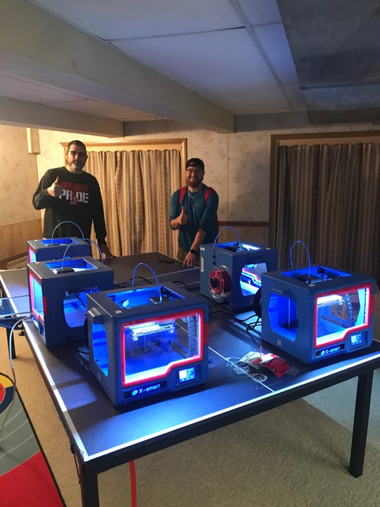 Homestead High School teachers Joe Ciurlik, left, and Jeff Patterson pose with the school's five 3D printers, which are pictured here in Ciurlik's basement. The two have been using the printers to create plastic components for masks for health care workers.