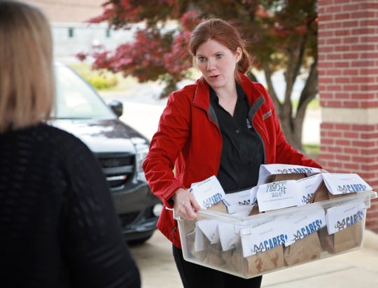 Tammy Hazel with The Grill at Whispering Woods carries a box loaded with meals into the East Side Baptist Church on Friday. The Grill at Whispering Woods and MH Cares gave 440 meals to churches in the Mountain Home area to give to those in need.