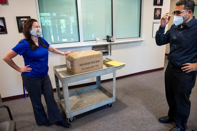 EMA director Christina Thornton accepts donated face masks from Beauty and Beyond owner Ashraf Hijaz at the Montgomery County Emergency Management Agency in Montgomery, Ala., on Monday, April 20, 2020.