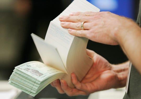 An unidentified printer looks over stimulus checks at the Kansas City Regional Financial Center in Kansas City, Mo.
