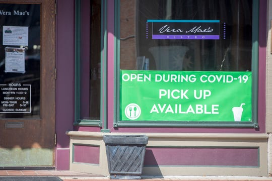 Signs signal restaurants which are still handling curbside service in downtown Muncie on Saturday, April 20. Most businesses have been closed to the public since the stay-at-home order from the state in March.