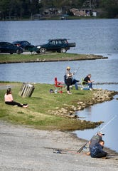 Those that want to fish still keep some distance along the shore of Old Hickory Lake at the dam recreation area in Old Hickory, Tenn. Monday, April 20, 2020.