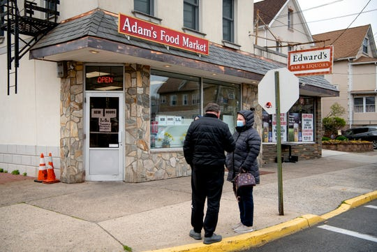 Adam's Food Market in Wallington, a small Polish market, is limiting occupancy to five customers due to the coronavirus and the need to social distance. Teddy Krystyniak, owner of the market since 1981, is closing two hours early allowing ample time for disinfecting and restocking the store. Customers wait to enter the store on April 20, 2020.