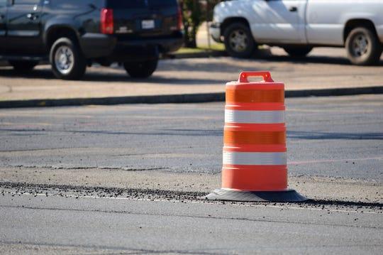 Orange construction barrel on a city street.