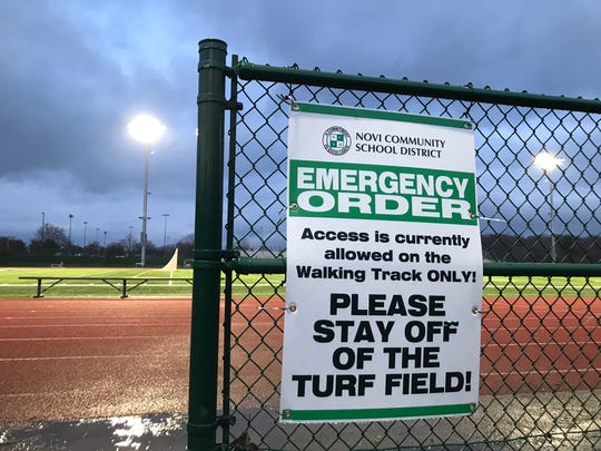 A sign right next to the gate to the football field at Novi High School