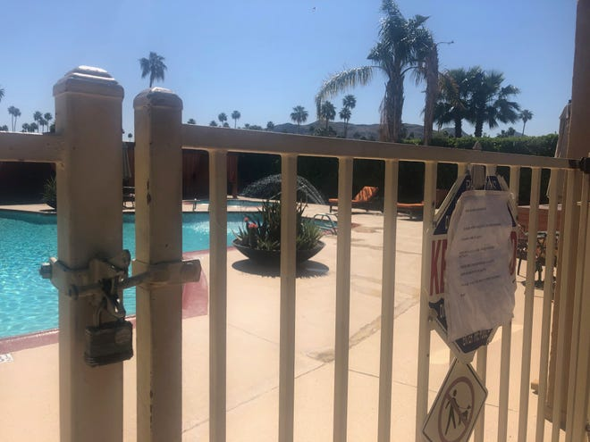 A padlock and warning sign are shown outside a Palm Springs apartment complex's swimming pool Monday, April 20, 2020. Private and public swimming pools across the Coachella Valley are closed to reduce the spread of coronavirus and residents say they rely on pools to keep cool during the summer.