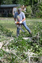 Santa Rosa County resident John Pettit works Monday clear away the brush and damage left behind after severe weather hit the area.