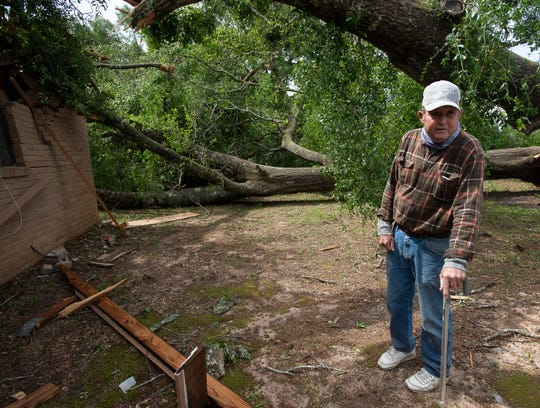 Santa Rosa County resident Wiley Keyser surveys the damage to his home after a line of thunderstorms rolled through the area Monday.