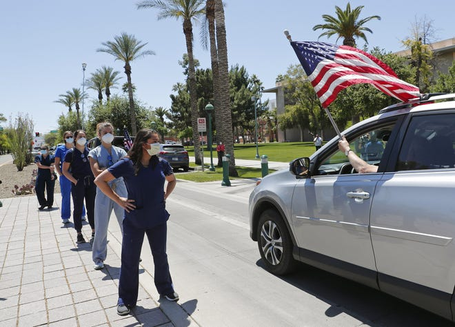 Health care workers stand in counterprotest in front of the Arizona state Capitol in protest of Gov. Doug Ducey's stay-at-home order to combat the coronavirus on April 20, 2020.