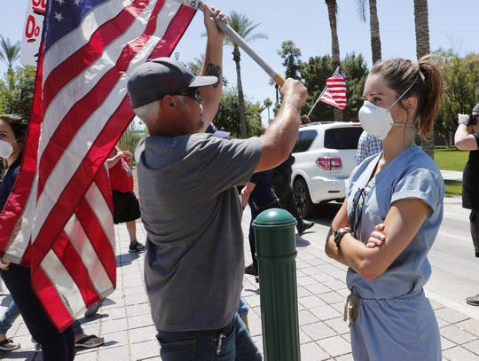 Banner University Medical Center ICU nurse Lauren Leander stands in counter-protest as people march toward the Arizona State Capitol in protest of Gov. Doug Ducey's stay-at-home order to combat the coronavirus April 20, 2020.