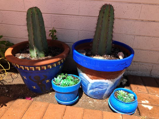 I planted cactus in pots on my front porch while I was on furlough. The pot on the left I painted years ago, but I painted the one on the right last week to seal it.