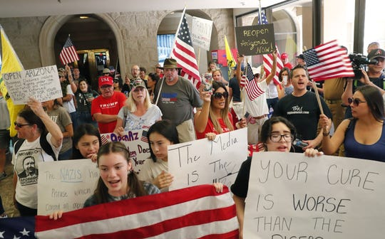 Protesters flood the lobby of the Arizona state Capitol Executive Tower in protest of Gov. Doug Ducey's stay-at-home order to combat the coronavirus April 20, 2020.