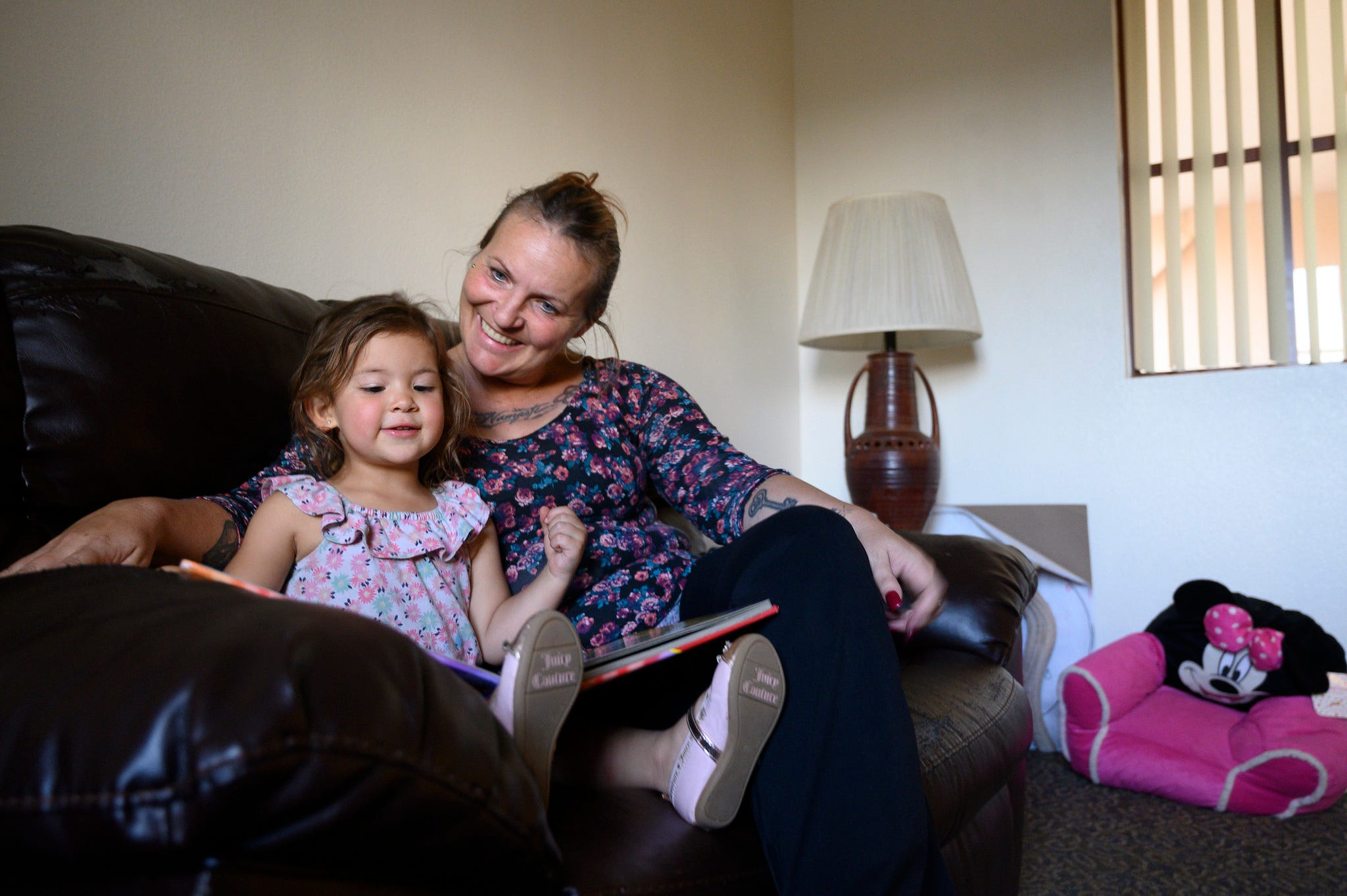 Rebecca Legate reads with her 3-year-old daughter, Nati. Legate, once homeless during one of Phoenix's hottest summers, now works for the Phoenix Rescue Mission.