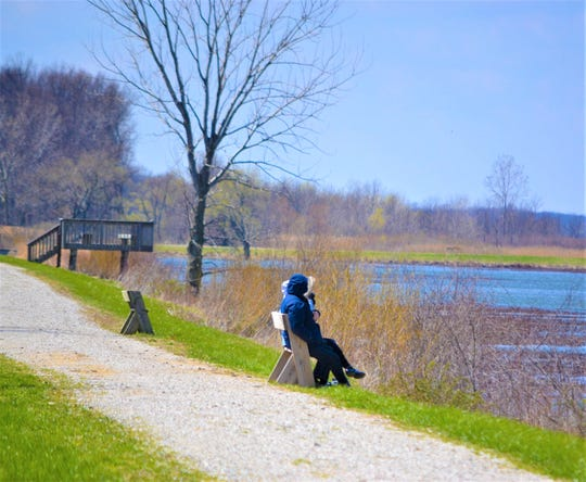 Although a strong wind kept a chill on the walking paths at Ottawa National Wildlife Refuge on Saturday, many locals still took hikes along the trails. Here, visitors take a break along the water's edge.