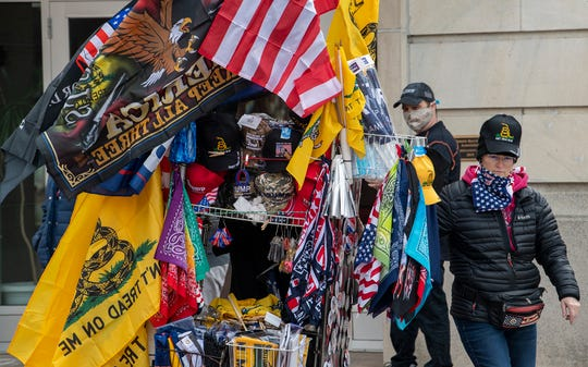"""A vendor sells memories of the rally. A """"Reopen Pennsylvania"""" rally in front of Harrisburg's Capitol building drew 2000 people to hear speakers and show solidarity."""