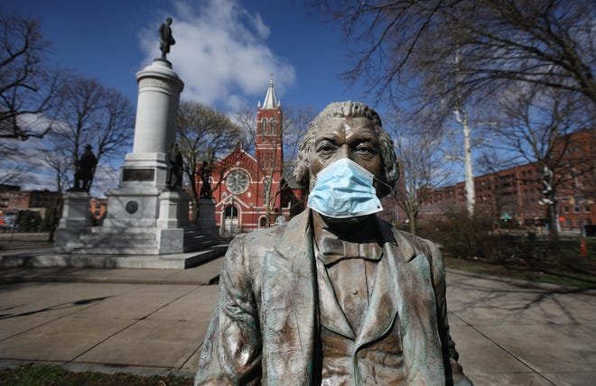 In a sign of the times, even a statue of Frederick Douglass is wearing a mask in downtown Rochester Monday, April 20, 2020. Someone put a mask on the statue, created by artist Olivia Kim, that stands in Washington Square Park.