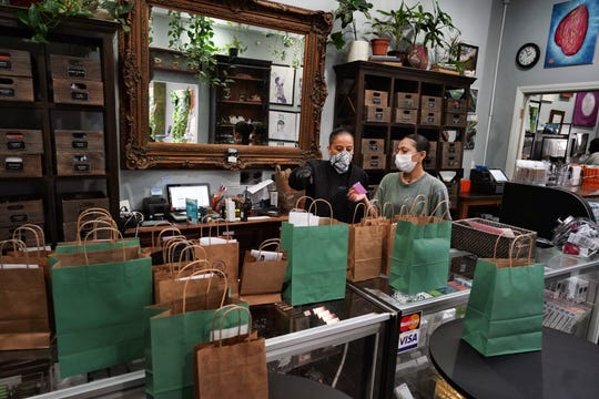 Wearing a protective mask and gloves, budtenders prepare orders for customers to pick-up at The Higher Path cannabis dispensary in the Sherman Oaks section of Los Angeles.