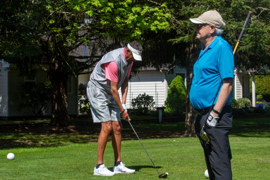 Michael De Mont, left, takes his turn after his friend Joe McDonald at the McNary Golf Club in Keizer on Monday, April 20, 2020.