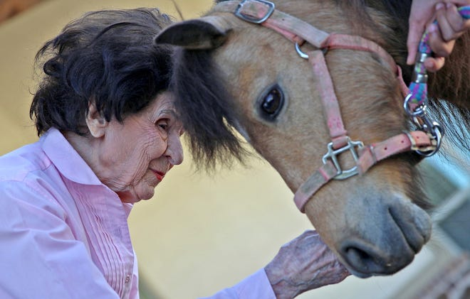 Jenelle Barron, left, pets Buttercup the pony at the New Haven Assisted Living and Memory Care of San Angelo on Monday, April 20, 2020. Restrictions in place due to the coronavirus have severely limited visits to residents so staff at the facility brought the horse in as a way to entertain them.