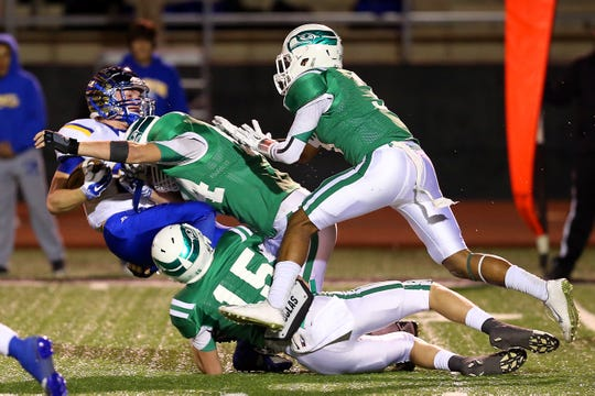 Wall's Lane Oliver delivers a big hit, with help from his teammates, during a 2014 playoff game against Brock.