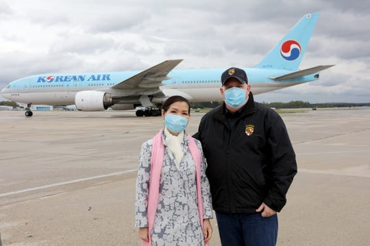 Maryland First Lady Yumi Hogan and Gov. Larry Hogan stand on the tarmac at Baltimore/Washington International Thurgood Marshall Airport on Saturday, April 18, 2020, as Maryland accepts thousands of COVID-19 test kits from South Korea.