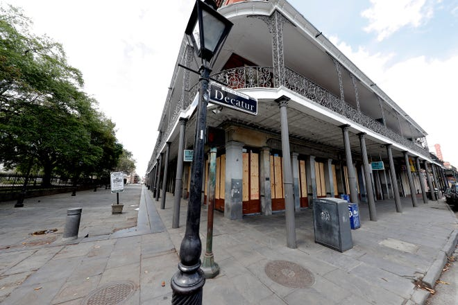 Boarded up businesses are seen along Jackson Square, normally bustling with tourists, in the nearly deserted French Quarter of New Orleans, due to the new coronavirus pandemic, Friday, March 27, 2020. While rich in history and culture, New Orleans is economically poor, and the people here are not necessarily well-positioned to weather this latest storm. (AP Photo/Gerald Herbert)