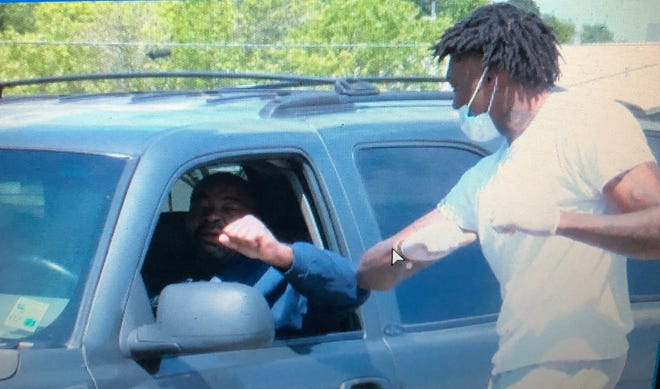 Boston Celtic forward Robert Williams elbow bumps a fan Saturday while handing out fish plates in Vivian.